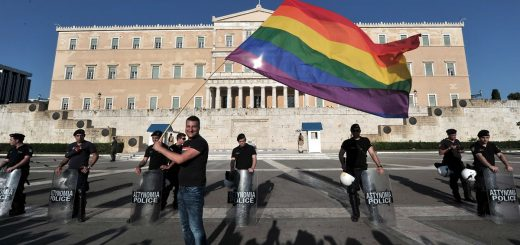A participant of the  Gay Pride event  waves a rainbow flag by police protecting the Greek parliament in central  Athens on June 9, 2012. Some 1000 people took part at a march organised by Greece's gay and lesbian community, with the main slogan ' love me, its for free' . AFP PHOTO/ LOUISA GOULIAMAKIARIS MESSINIS/AFP/GettyImages ORG XMIT: