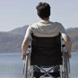Caucasian man in wheelchair sitting on dock