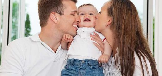 Close-up of mother and father kissing their child